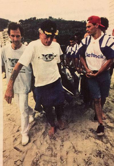 Flipper ao sair do tanque, levado por Ric O'Barry, Marco Ciampi e equipe
